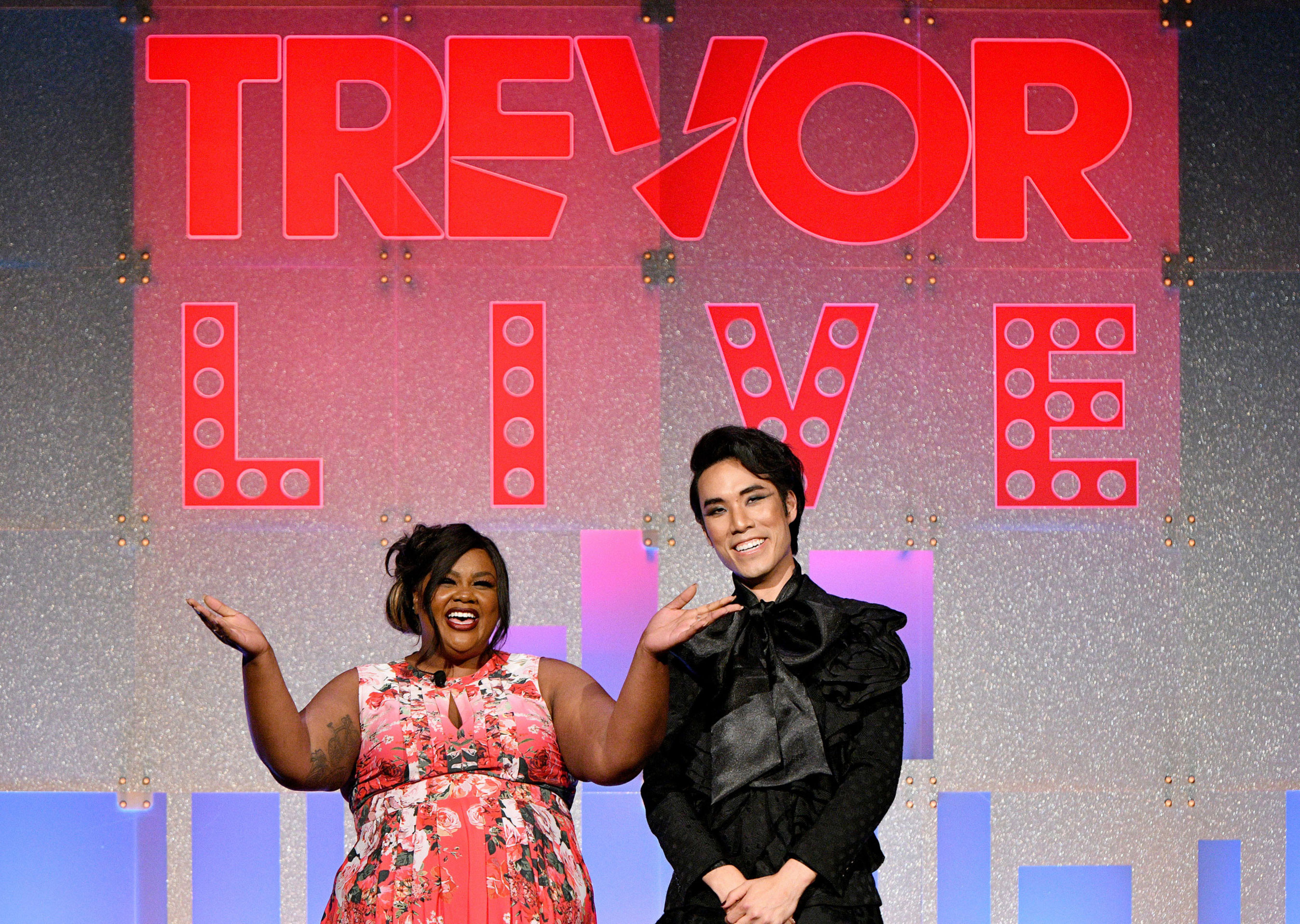 Hosts Nicole Byer and Eugene Lee Yang in front of the TrevorLIVE stage backdrop